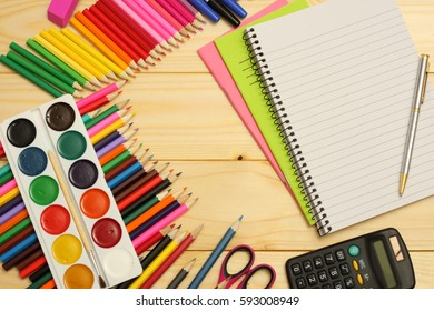blank paper notebook with colored pencils, pains, calculator for  school and student education on wood background