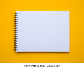 Blank paper notebook or notepad on yellow background