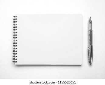 Blank paper notebook or notepad and a pen on white background