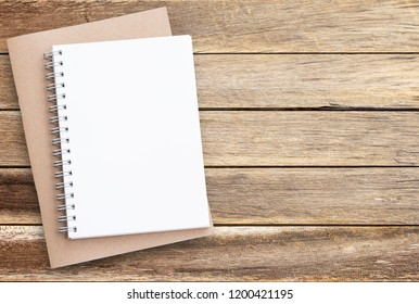 Blank paper notebook on brown wooden table background. Top view with copy space (selective focus). Office desk table concept with copy space for any design.