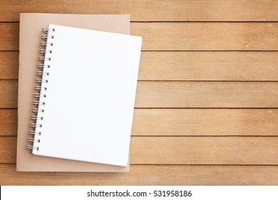 Blank paper notebook on brown wooden table background. Top view with copy space (selective focus). Office desk table concept.
