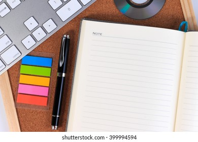 Blank paper or blank notebook on office table with bookmark keyboard and notebook. Open blank notebook, note, paper on office table. Blank notebook / paper with keyboard and bookmark on office table.