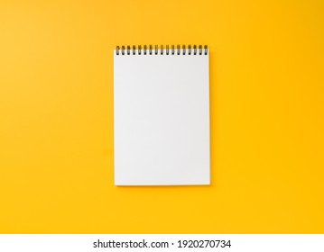 Blank paper notebook with spiral on yellow background, top view, flat lay with copy space