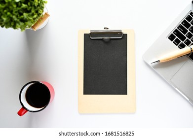 Blank paper on the clipboard With laptops and coffee On the morning office desk