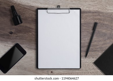 Blank Paper on Clipboard with phone and Pen  on wood table background.Copy space