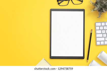 Blank paper on folder on yellow office desk with copy space beside. Hero, header image, top view, flat lay composition.