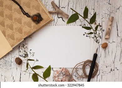 Blank paper on wooden background with pressed flowers and old book