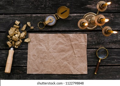 Blank paper page with copy space for treasure map, compass, magnifier loupe and shovel full of gold nuggets ore on wooden table. Treasure hunter or gold miner concept.