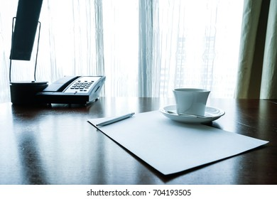 Blank paper with pen, coffee cup and telephone on wood table front of windows with white curtains.
