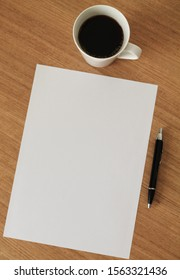 Blank paper with pen and cup of coffee on wooden table