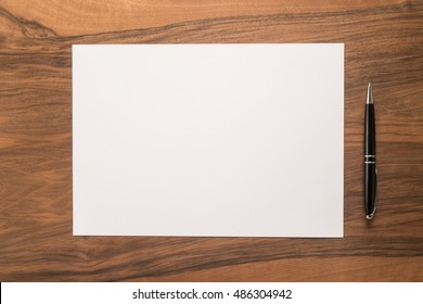 Blank paper and pen on wooden background