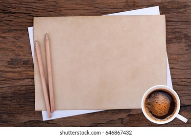 blank paper with pencil and a cup of coffee on wooden