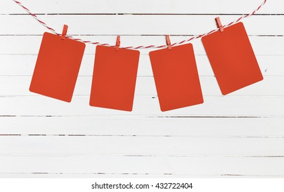 Blank paper or photo frames hanging on the red striped clothesline . Wooden background. Template for your text.