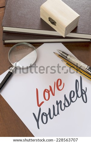 Blank paper with phrase Love Yourself on desk.