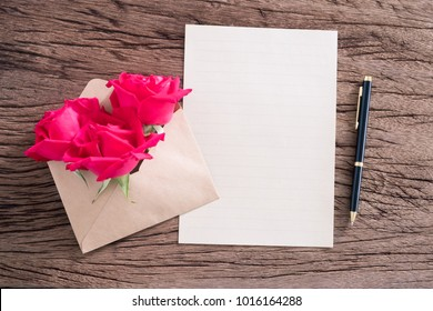 Blank paper with red roses on wooden background