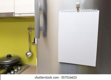 blank paper sheet hanging on fridge door