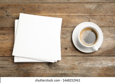 Blank paper sheets for brochure and cup of coffee on wooden background, flat lay. Mock up