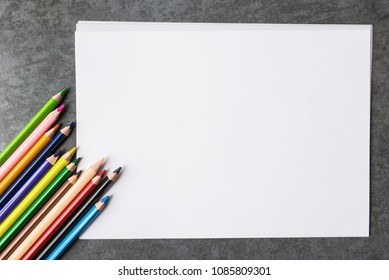 Blank paper sheets and multicolored pencils.