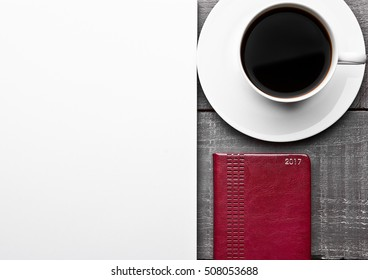 Blank paper for sign with coffee and note book and note book on wooden board