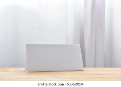 Blank paper table card on wooden table