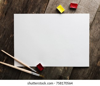 Blank paper with watercolor and brushes on the wooden table for mockups.