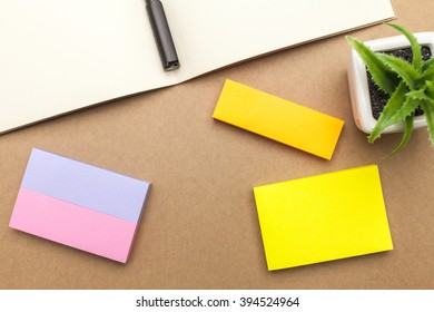 Blank paper,book,pen and plant on brown background