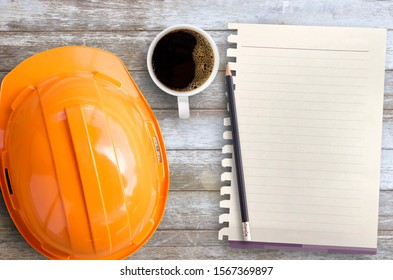 Blank paper,orange safety helmet,notepad or notebook and cup of coffee on brown wood table background. Top view with copy space for text or any design. White paper on table wood show paper concept
