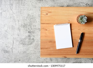 Blank paper,Succulent,Laptop computer and pen on wooden table with copy space