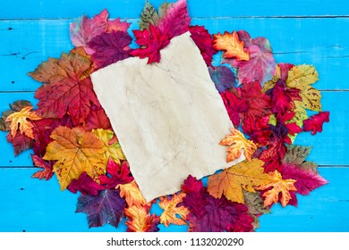 Blank parchment paper sign with colorful fall leaves border on antique teal blue wood background; Thanksgiving, Halloween,  seasonal autumn holiday sign with copy space
