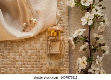 Blank perfume bottle with gold and marble cup in front of a brunch of cherry blossom and a jewelry with pearls. Photography in beige tones