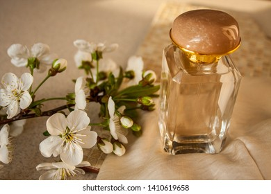 Blank perfume bottle with gold and marble cup in front of a brunch of cherry blossom. Photography in beige tones