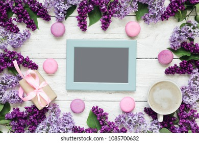 blank photo card in frame made of lilac flowers with coffee cup, gift box and macaroons over white wooden table. mock up. flat lay. top view. mothers day background
