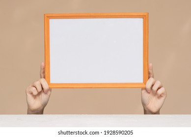 A blank photo frame border with copy space in the hands close up.