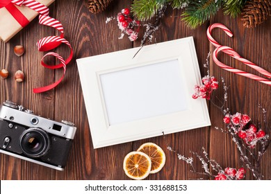 Blank photo frame with christmas gift box, pine tree and camera on wooden table. Top view