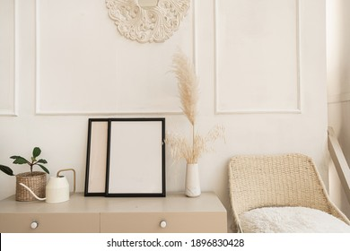 Blank photo frame with copy space on table. Fluffy reeds, pampas grass bouquet, home plant, rattan chair against white wall. Comfortable modern interior design. Stylish bright living room.