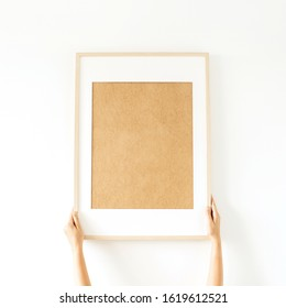 Blank photo frame with empty mockup copy space in women's hands. Minimal watercolor art concept.