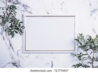 Blank photo frame and green plant over marble table background. Women Day. Mockup. Flat lay, top view