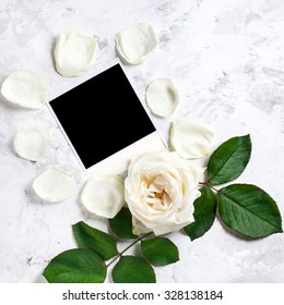 Blank photo frame near white rose and petals on white marble background