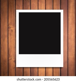 blank photo frame on brown wood plank background