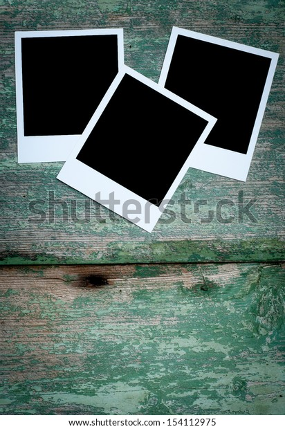 blank photo frame on green wooden background close up