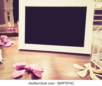 Blank photo frame on the wood table with flower,digital effect vintage style