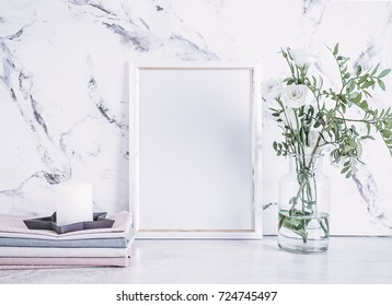 Blank photo frame, stack of fabrics and white flowers on vase over marble table background. Mockup