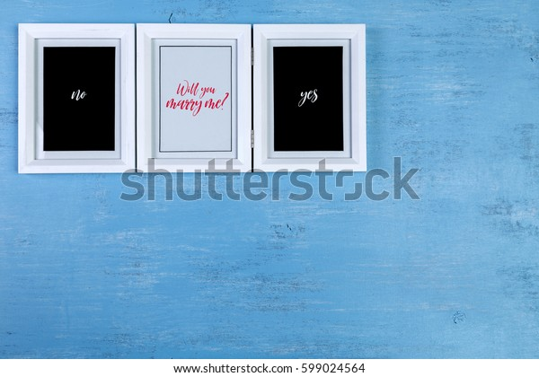 Blank photo frames on blue wood background. Will you marry me? Painted scraped wooden board. Grunge plywood texture or pattern.
