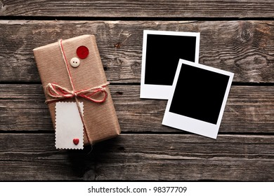 Blank photo frames and vintage gift box (package) with blank gift tag on old wooden background.