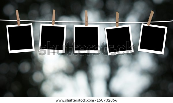 Blank photographs hanging on a clothesline against a Bokeh lights background