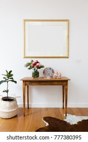 Blank picture frame above a side table with flowers and pot plant