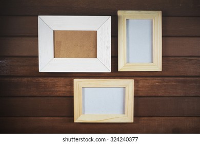Blank picture frame on old wooden wall. Vintage effect.