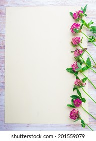 Blank picture frame paper with plants on wooden table