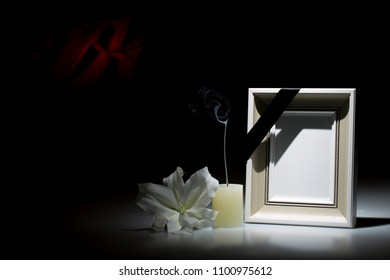 Blank picture frame, with smoky candle and white lily flower on dark background with red decoration