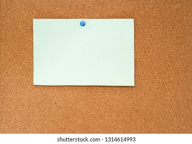 blank piece of pale paper pinned to a cork bulletin board